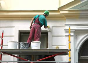 An exterior painter working on a home in Guilford